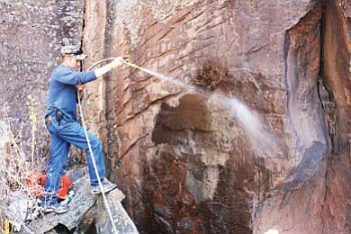 Photo/U.S. Forest Service, Southwestern Region, Kaibab National Forest<br< Paul Thomas Carter uses a hose and pump that firefighters carried to Keyhole Sink to spray off a mud application during removal of vandalism evidence.