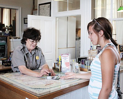 Clara Beard/WGCN <br> Mary Barbee stamps a visitor's passport at the Williams-Forest Service Visitors Center.