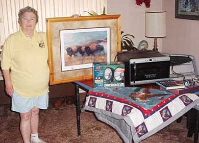 Submitted photo<br> Williams Lions Club member Edie Phillips displays prizes that will be auctioned during a silent auction Sept. 4.
