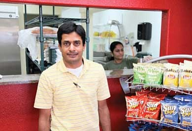 Nimo Patel waits on a customer while his wife Shital prepares a sandwich. The couple recently opened Big Town Hero sandwich shop, where the bread is made fresh from scratch every day.