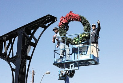 Clara Beard/WGCN<br> Victor Duarte and Jesus Salazar hang the last wreath on the Gateway Arch on Grand Canyon Boulevard in preparation for the approaching holiday season. Williams-Grand Canyon Chamber of Commerce officials were busy this past week, adorning streetlamps with wreaths and lights.