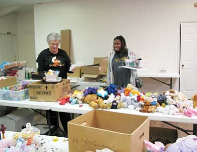 Lynda Duffy/WGCN<br> Volunteers Julia Glaab (left) and Teri Brammann fill shoeboxes Oct. 27 at Walker Hall. Donations and volunteers are still needed.