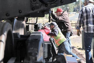 City of Williams maintenance crew members along with Grand Canyon Railway employees and others guide a vintage tank car  onto a length of railroad track in Glassburn Park. Ryan Williams/WGCN