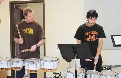 Drumline instructor Kevin McElwee (left) and Julio Belmontes work on stick control during a rehearsal last week at Williams Elementary-Middle School. Marissa Freireich/WGCN
