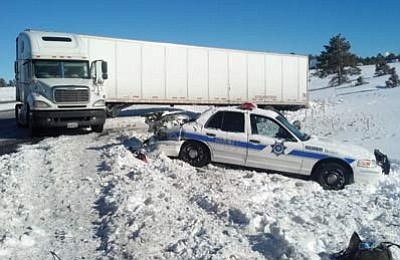 An Arizona Department of Public Safety (DPS) patrol car sits damaged on the side of I-40 near milepost 160 after a semi tractor-trailer rig lost control and hit the vehicle injuring officer Greg King. Submitted photo