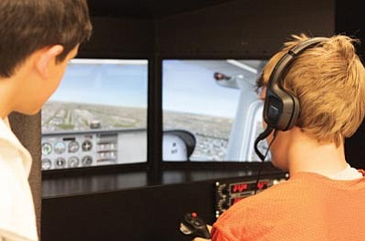 Williams Middle School students try their hands at flying using a First Flight Education simulator during a science and technology night in October. Clara Beard/WGCN