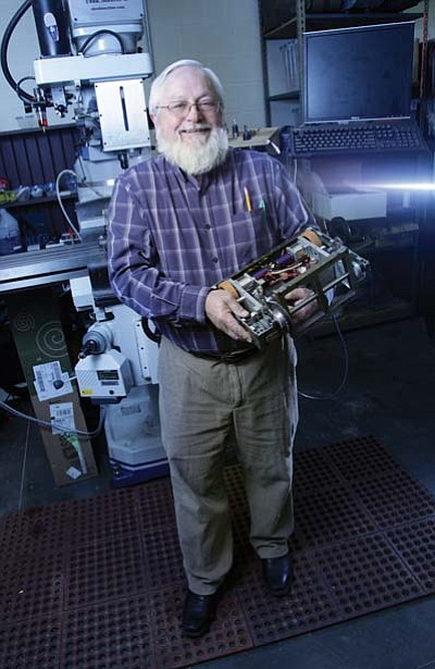 Larry Gutshall holds one of the BattleBots his students designed and built. Ryan Williams/WGCN