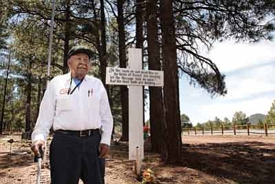 Perico Avila stands in front of the cross of the unknown soldier in the Williams Cemetery. Avila organizes the Memorial Day service that takes place Monday at 11 a.m. at the cemetery. Ryan Williams/WGCN