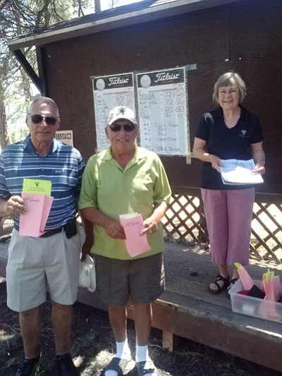 Golf Tournament Chairperson Kris Vasquez gives Steve Jenner a book on the Grand Canyon and two Grand Canyon Railway  tickets for completing the longest drive of the day. Submitted photo