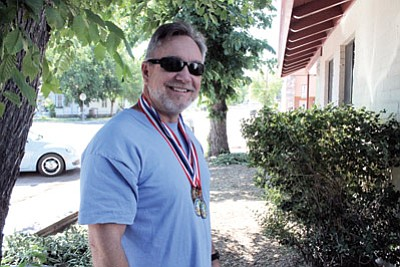 George Bardwell stands with medals he won at recent track meets. Ryan Williams/WGCN<br /><br /><!-- 1upcrlf2 -->