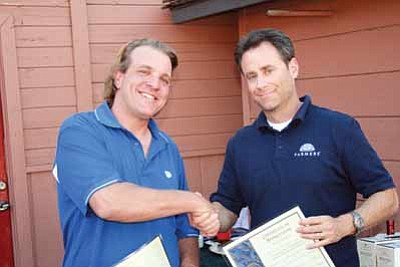Outgoing Rotary President Steve Lovas (left) congratulates Brian Prager on becoming the President of the Williams Rotary Club. Prager plans to continue the local service club's focus on supporting youth activities and scholarships in Williams. Photo/Jim Bultema