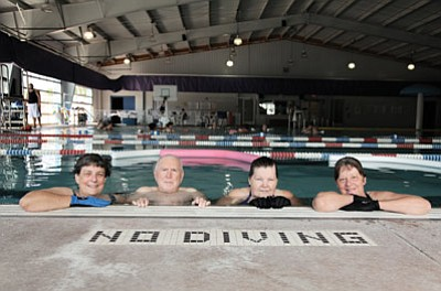 Gene Hill (second from left), Sherry Sleeper (far right) and two other water aerobicizers take a quick break during a morning deep water aerobics class at the Williams Aquatic Center. Ryan Williams/WGCN