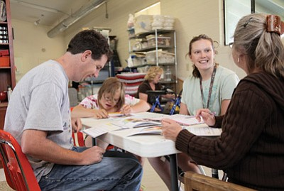 From left: Mark Konkel, Guine Michelson and Carisa Stilwell work on calendar skills like naming the days of the week and holidays at Camp Civitan's Day Treatment and Training Program for Adults. Ryan Williams/WGCN