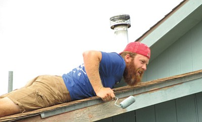A Bike and Build member paints a hard to reach location at a home in Williams. Submitted photo
