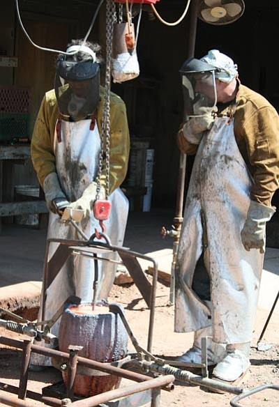 Foundry workers pour hot metal into a mold. Photo/Neil Logan