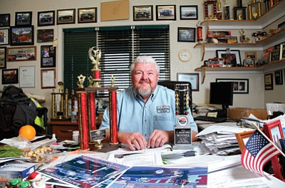 Local drag racer Larry Pittenger sits in his office at L.P.'s Excavating amid his collection of racing trophies and photos. Ryan Williams/WGCN