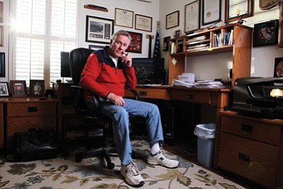 Rodger Ely takes a short break in his home office. Ely estimates he volunteers 40 hour a week with a number of organizations — making a place to stay organized a necessity. Ryan Williams/WGCN