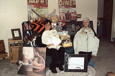 Sabrina Sartor (left) and Barb Parenteau display some of the raffle prizes available at Opry Night Friday at the Williams Rodeo Barn. Proceeds benefit Williams Habitat for Humanity. Submitted photo