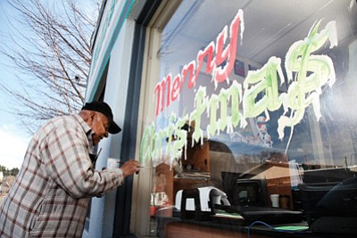 "Fred ""Perico"" Avila paints a holiday message on the window of the Williams-Grand Canyon News. Ryan Williams/WGCN"