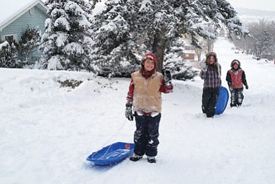 Tavish Fergus, Corinna Weller and Kiera Fergus enjoy sledding New Year's Day in Williams. A storm that began Dec. 31 dropped 14 inches of snow in Williams. Connie Hiemenz/WGCN