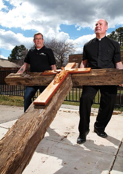 Family Harvest Church Pastor Tim Milner (left) and Father Kilian McCaffrey of St. Joseph's Catholic Church display a cross made out of railroad ties. Local church members plan to carry the cross through Williams on Good Friday, April 3. Ryan Williams/WGCN
