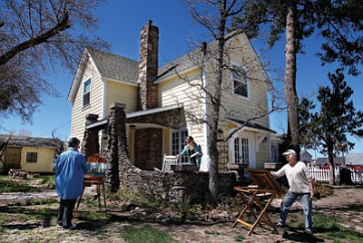 From left: Lupe Miranda-Sapp, Chris Mills and Kris Williams paint en plein air in front of the historic Yellow House. Ryan Williams/WGCN