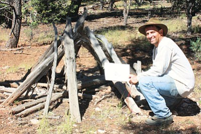 Archaeologist Neil Weintraub kneels next to a brush shelter discovered on Kaibab National Forest.  Photo/KNFS