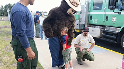 Smokey the Bear visits with students during KinderCamp at the Williams Elementary school June 12. Kids spent time with Smokey and Forest Service Fire Fighters gave the kids a tour of a fire engine. Photos/Deniz Chavez