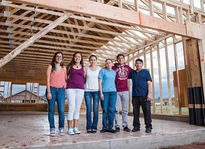 Jackie Lopez, Ximena, Veronica, Josefina, Rafael and Jose Hernandez stand in the garage of the Hernandez family's new Habitat for Humanity home.  Ryan Williams/WGCN