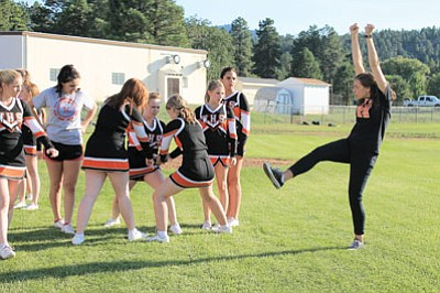 High school cheer coach Lauren Likovich demonstrates a move during a cheerleading practice.