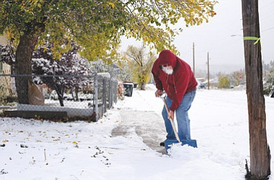 Lawrence Jaramillo shovels snow off his sidewalk on Fourth Street in Williams Nov. 4, during the city's first snowfall of the season. Ryan Williams/WGCN