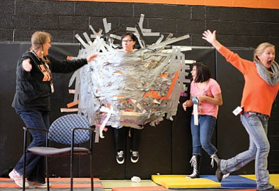 Williams Elementary-Middle School employees Sue Hamilton and Halley Rocha remove the chair from underneath principal Carissa Morrison during a PTSA fundraiser Nov. 19. Students purchased a strip of duct-tape for $1 and secured Morrison to the wall. Ryan Williams/WGCN