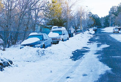 Cars sit plowed in along Williams streets after the city switched from plowing snow into berms in the middle of the street to plowing snow to the side of the street, surprising many residents in the process. Wendy Howell/WGCN