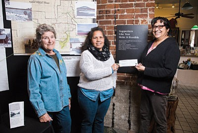Grand Canyon Coffee and Cafe owner Anna Dick presents a $100 donation to Margaret Hangan and Andrea Dunn with the Williams Historic Photo Project. Dick sells apple pie pieces with real gold flecks to raise money for the project. Ryan Williams/WGCN