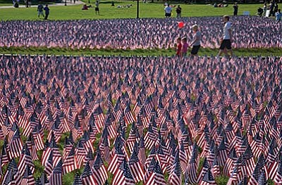 People walk through 20,000 flags that represent every Boston soldier who died in a war in the last 100 years. Adobe Stock photo