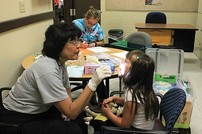 Coconino County Public Health Services District employee Jenny Garcia gives a Williams Elementary-Middle School KinderCamper a tooth checkup.  Wendy Howell/WGCN