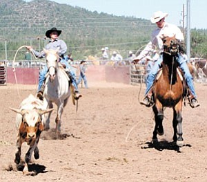 Two working cowboys form a team in calf roping during last year¹s Cowpunchers Rodeo. Working cowboys can be found at the Bob Dean Rodeo Grounds this weekend when the Cowpunchers return to Williams for their reunion rodeo. Cowboys and cowgirls of all ages will complete against one another throughout the weekend.