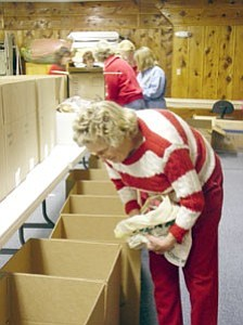 Williams resident Bea Johnson helps ESA members pack boxes for service personnel Dec. 1.