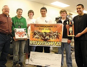 The victorious Slab Crabs proudly display their prizes. Pictured from left is instructor Larry Gutshall, Aaron Buchmoyer (holding the base of the winning battlebot), Kevin Duffy, Jesus Martinez, Andrew Eastland and Juan Hernandez, holding the trophy. Team member Rene Meraz is not pictured. The Slab Crabs will represent Arizona in a national battlebot competition later this month in Miami, Fla