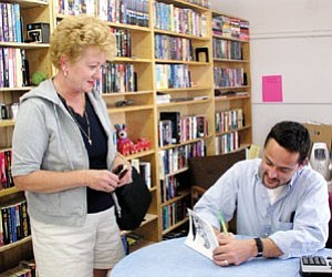Local author Patrick Whitehurst signs his new book ‹ available at Whistle Stop Books, 117 W. Railroad Ave. ‹ for buyer Lynn Riggle