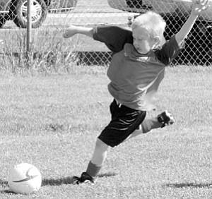 U6 boys AYSO Red Rockets player Max Schramm gets ready to kick it at a home game in Williams this past weekend.
