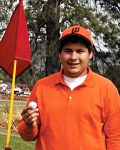 Senior Mathew Verser shows off his lucky golf ball at Elephant Rocks golf course. Verser hit a hole-in-one April 5.