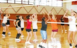 Members of the Lady Vikes get a work out over the volleyball net during practice August 9.
