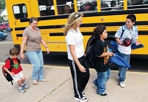 Doris Ann Mertz, Safe Routes to School coordinator, walks with children and a parent to their school bus. International Walk to School Day is scheduled for Oct. 3.