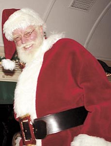 The one and only Santa Claus smiles to passengers after boarding the Polar Express™ train.