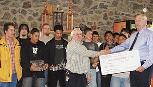 Members of the Williams Slab Crabs deliver their winning check to Williams High School Principal Steve Hudgens. The WHS Battlebots, such as the Slab Crab Revolution, won three awards during the recent state competition in Phoenix, including first and second place and an engineering award.