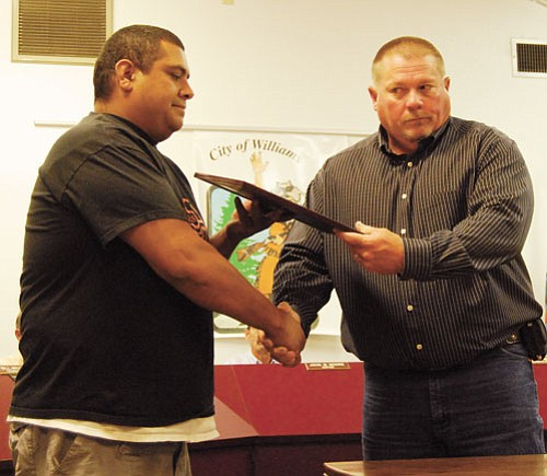 <br>Patrick Whitehurst/WGCN<br> Williams Police Chief Herman Nixon (right) shakes hands with Mike Atencio after giving him a plaque for his part in helping authorities apprehend a wanted suspect in Williams.