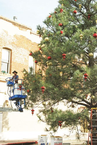 """<br>Patrick Whitehurst/WGCN<br> The Mesa-based group Christmas Decorators, with the """"Magic of Christmas in Williams,"""" prepare and decorate the community Christmas tree in anticipation for this year's tree lighting, slated for this Friday at 6 p.m. Entertainment will begin near the corner of Second Street and Route 66 at 4:30 p.m."""