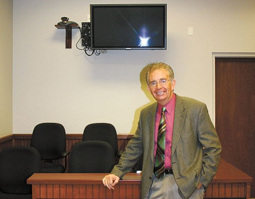 <br>Patrick Whitehurst/WGCN<br> Williams Judge Bill Sutton stands beside the video system at the Williams Justice Court. The system allows live court hearings without travel to Flagstaff.