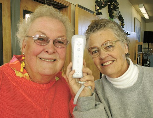 <br>Patrick Whitehurst/WGCN<br> Penny Joy (left) and Linda Henderson show off the Wii controller at the Williams Senior Center Jan.8.